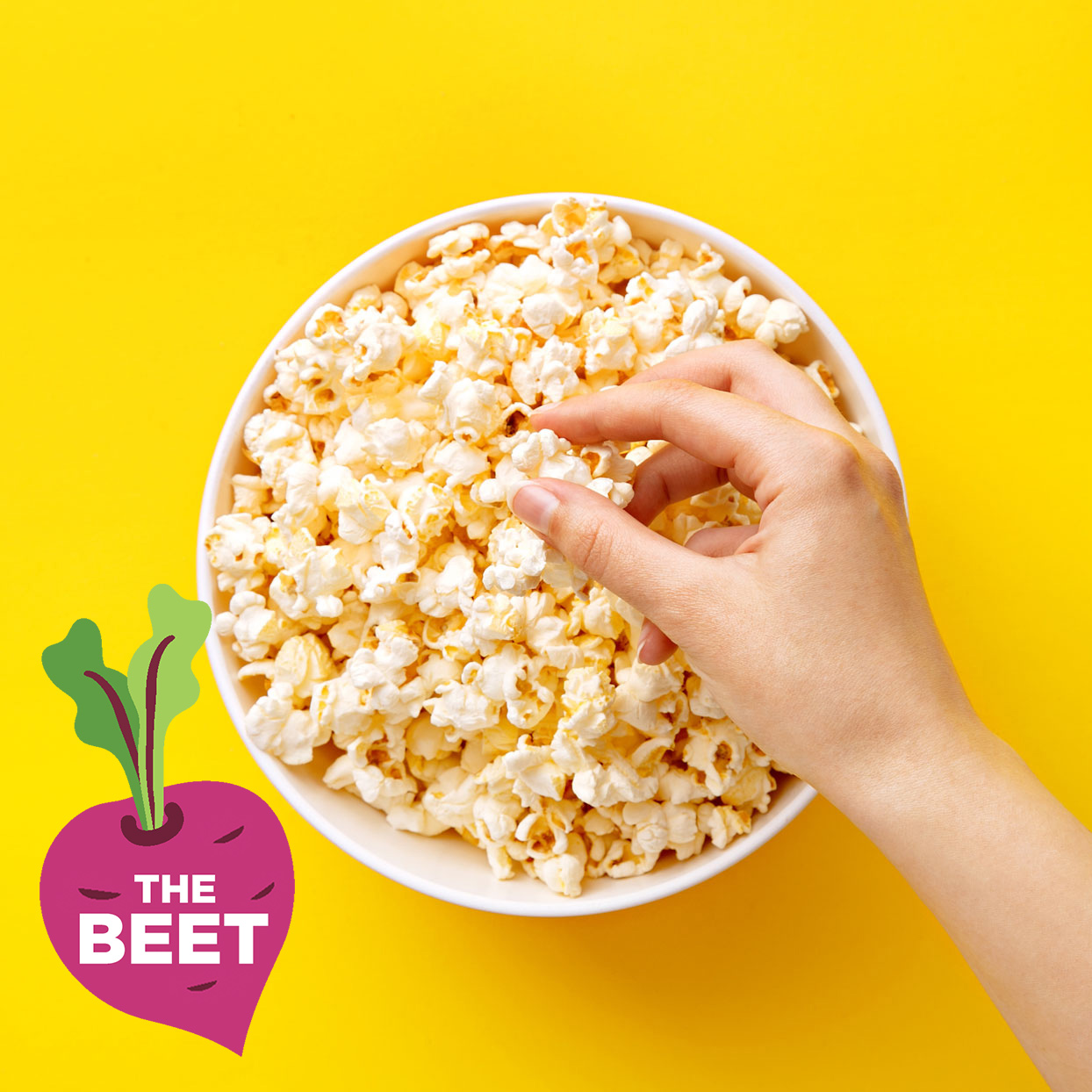 Hand getting popcorn from a bowl