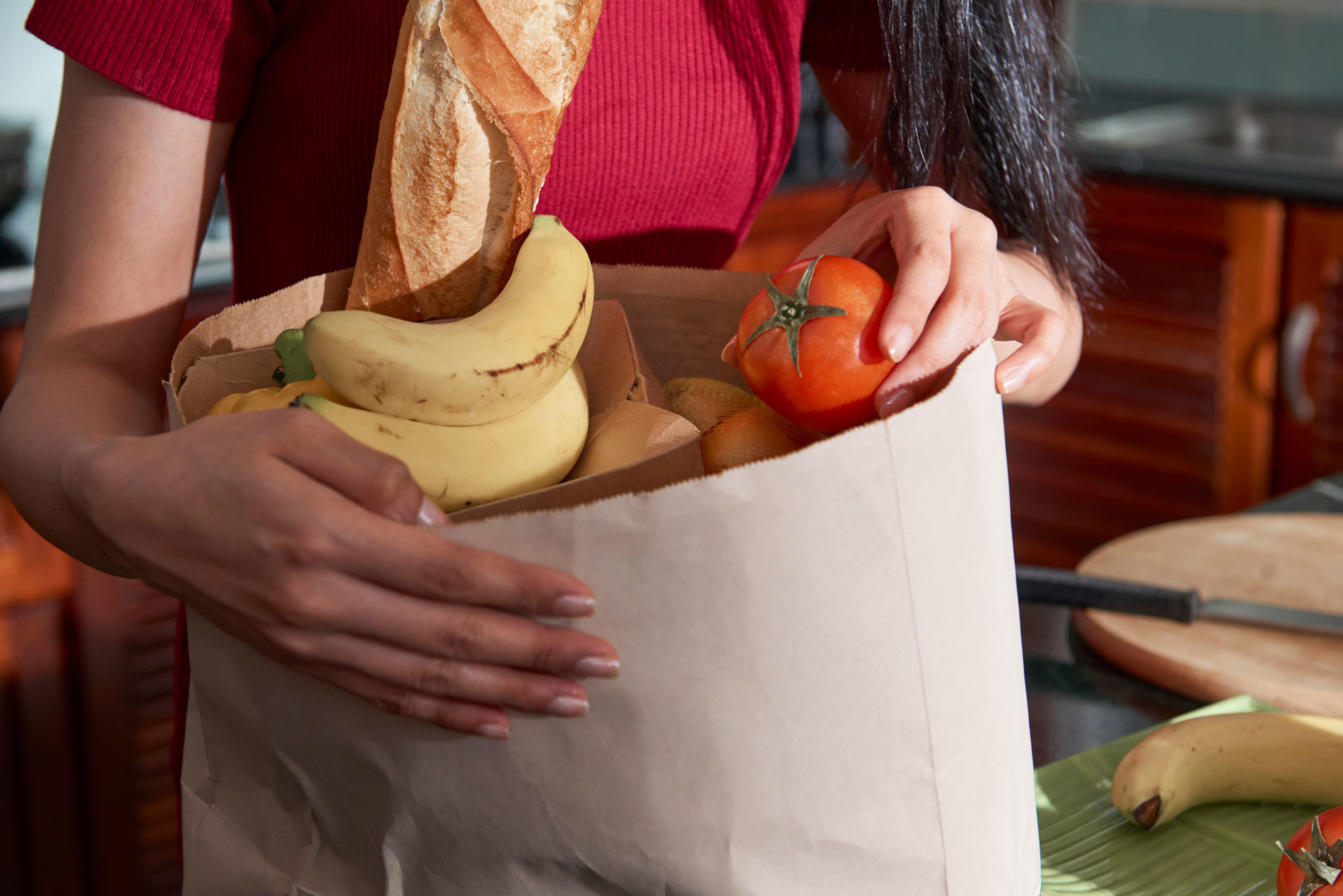 Woman unloading groceries from a paper bag