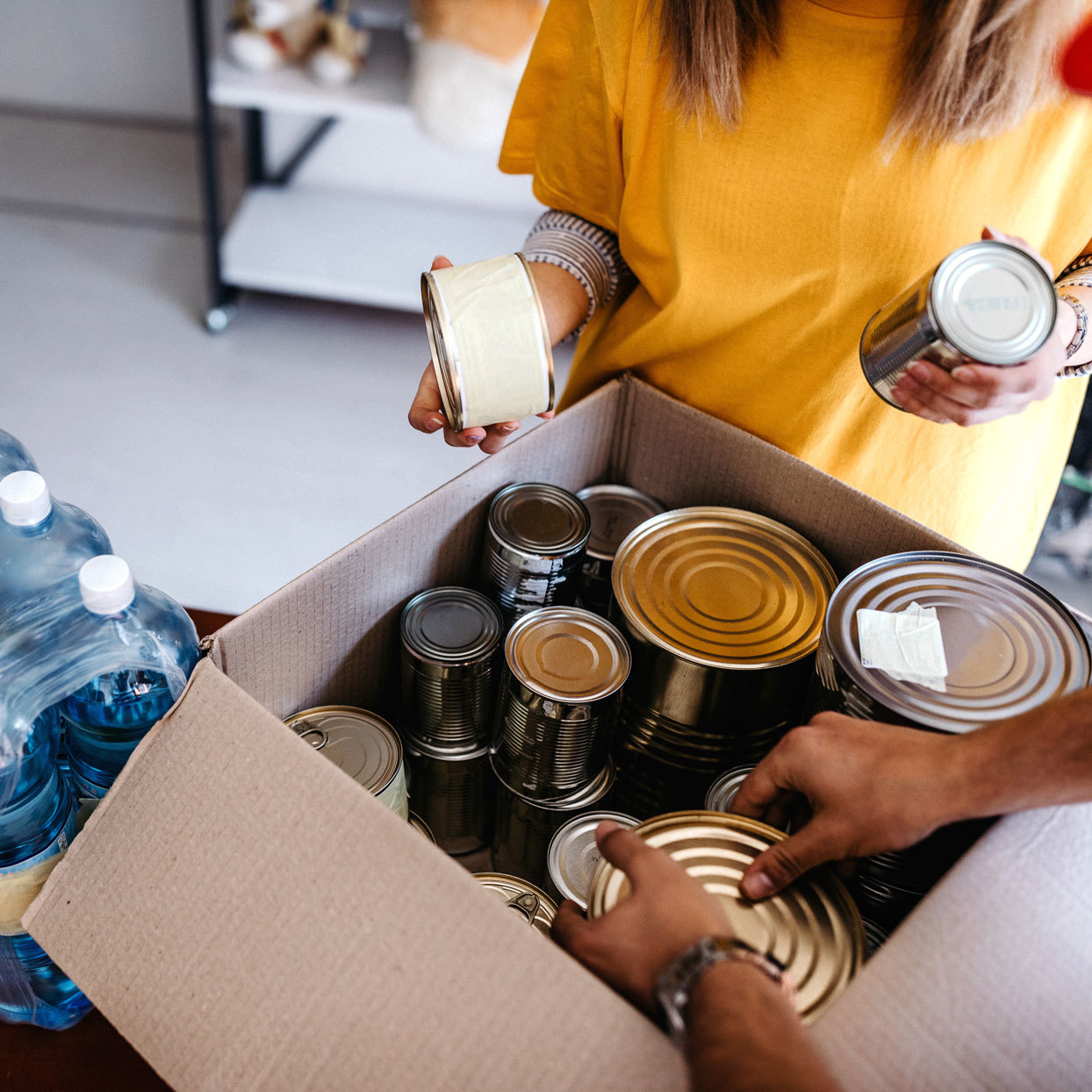 people going through a box of canned goods