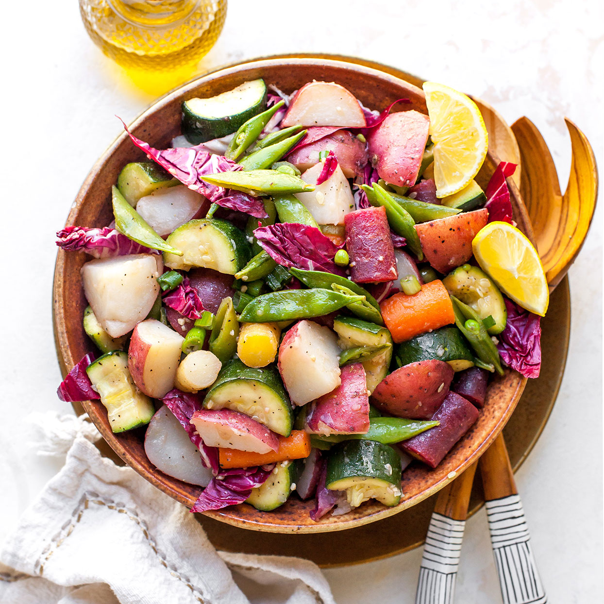 In Italy, this potato salad is known as Russian Salad. It has a thousand versions, most of them bound with plain or garlic mayonnaise. In this one, lightly steamed vegetables are splashed with vinegar while still hot, so they absorb the pungent aroma and flavor. A lemony vinaigrette binds the vegetables together. This salad looks especially pretty when made with red-skinned new potatoes and served in a cupped leaf of red radicchio. Butter lettuce or ruffled kale makes a nice presentation too.Source: EatingWell Magazine, Charter Issue 1990