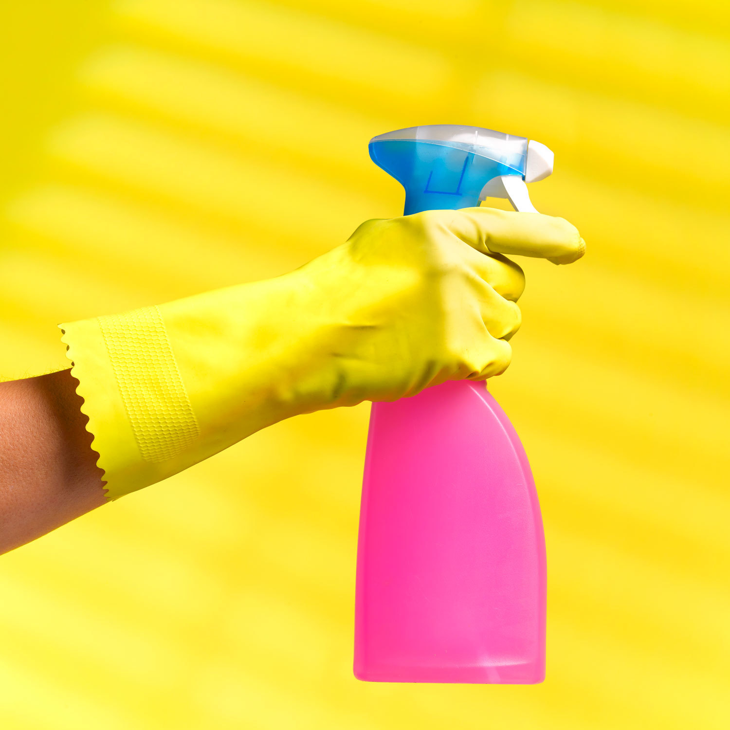 Cleaning gloved hand holding pink spray bottle on a yellow background