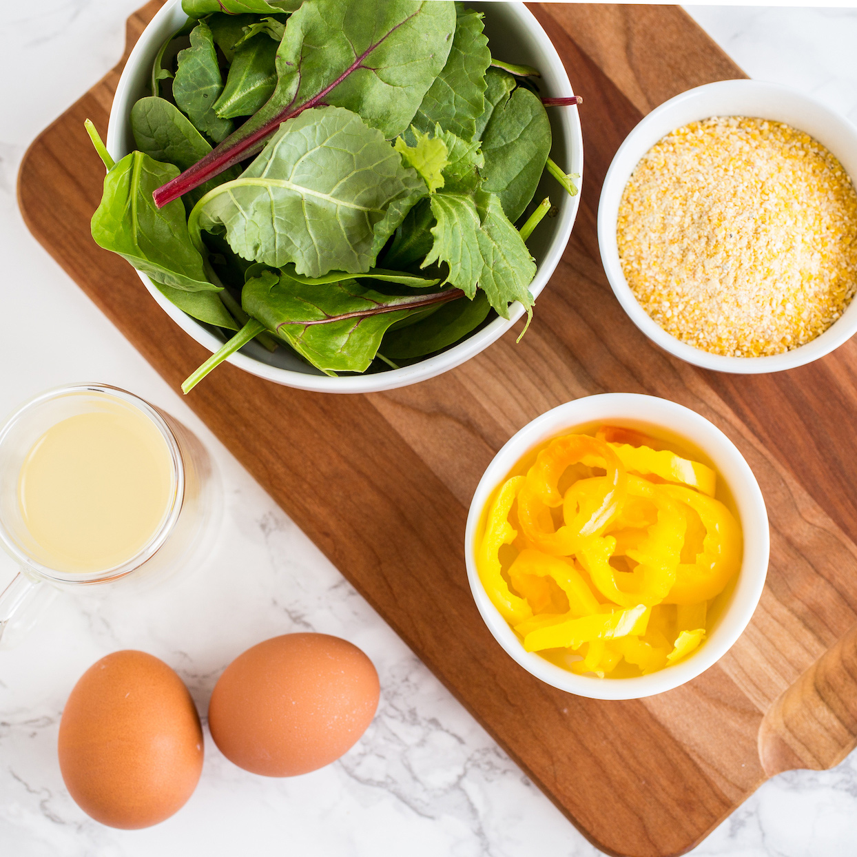 Eggs. salad greens, peppers, and polenta