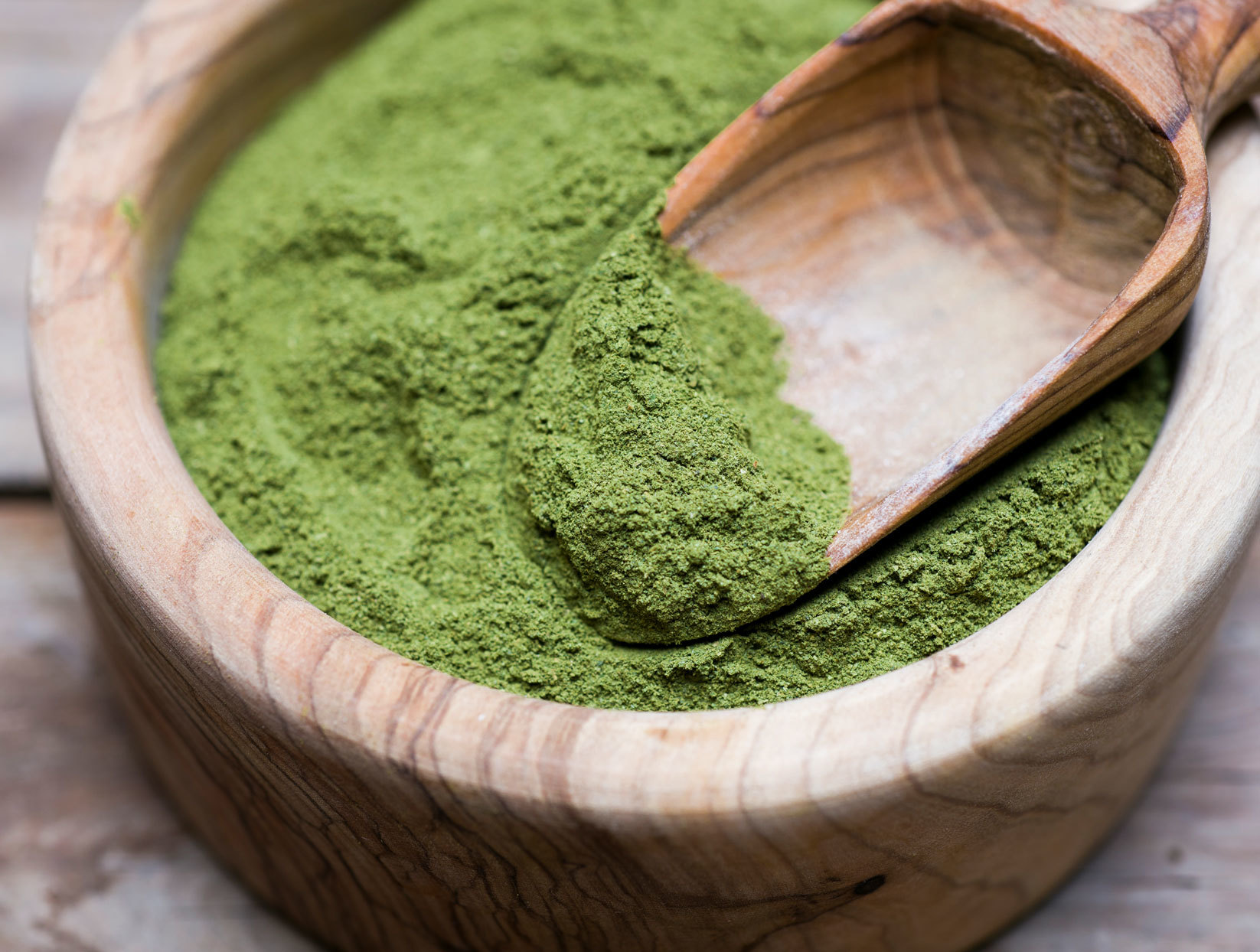 Moringa powder in wooden bowl with wooden scoop