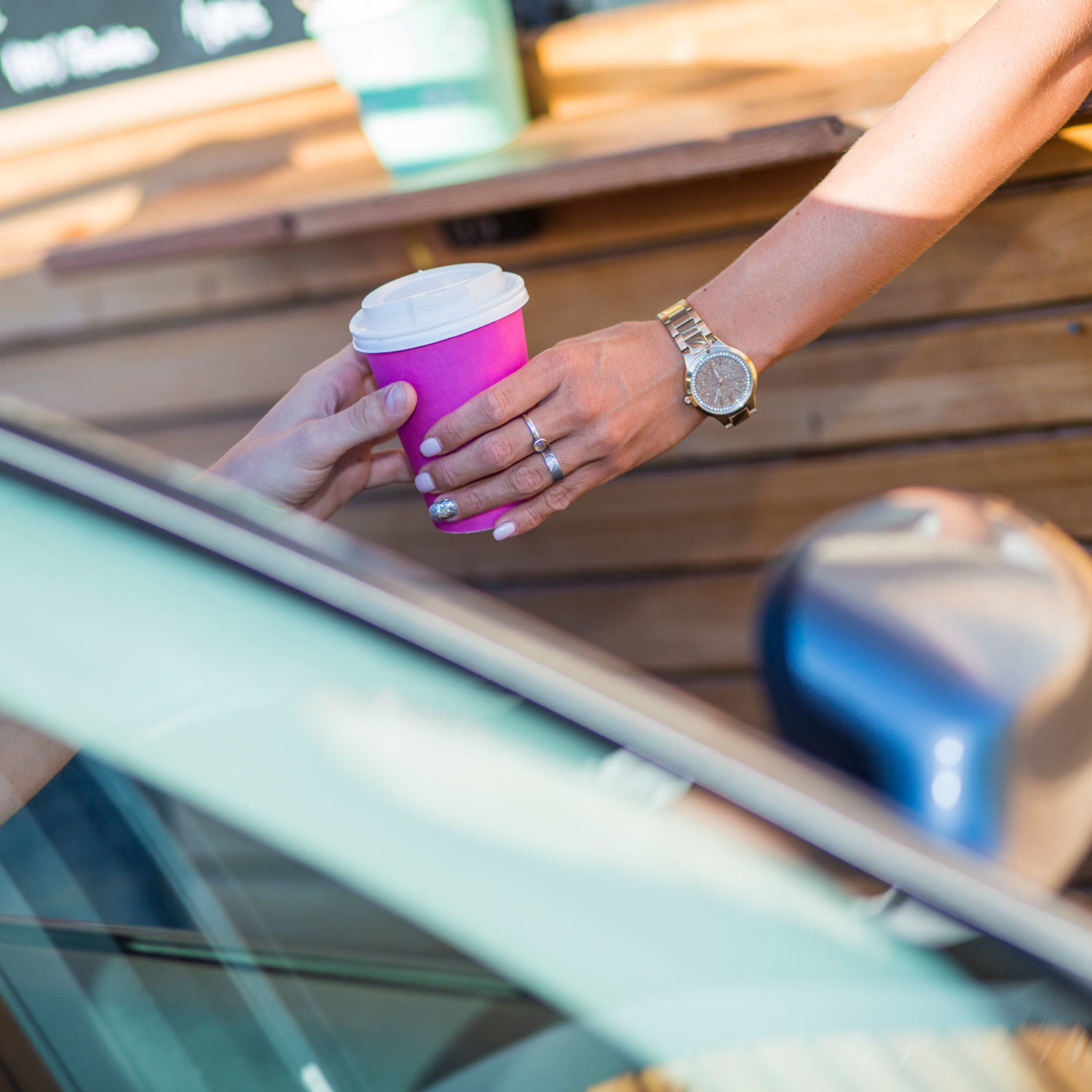 arm handing coffee to someone in a car at a drive thru