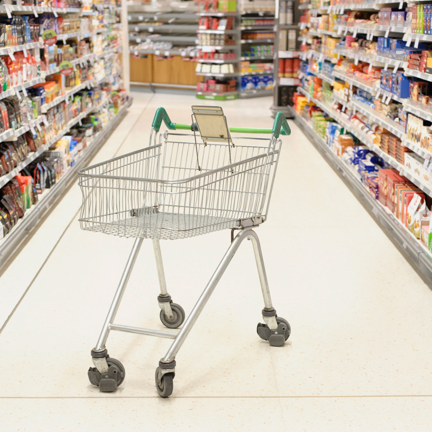 empty grocery cart in a grocery store aisle