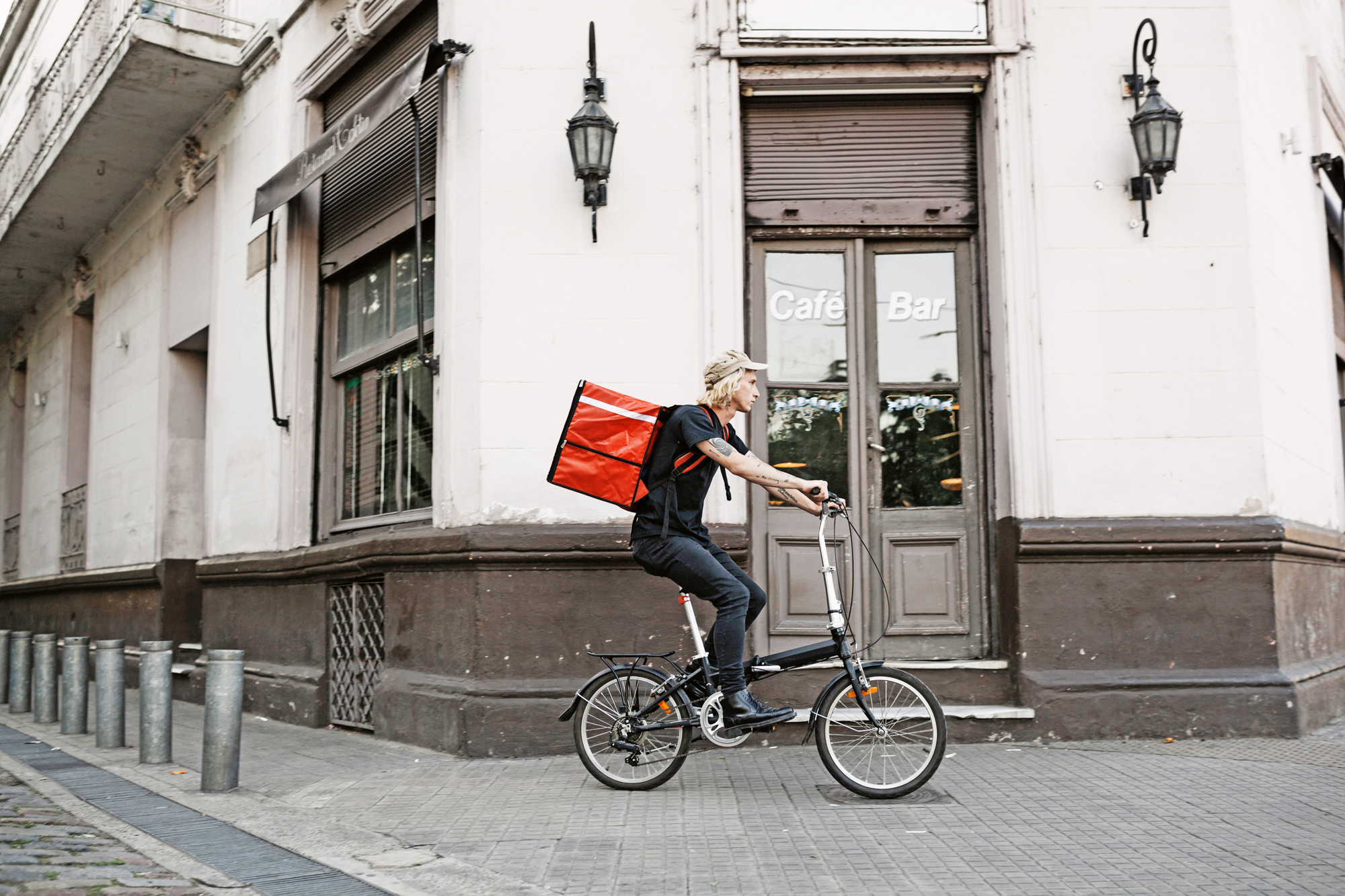 Young delivery person cycling with a big food courier bag.