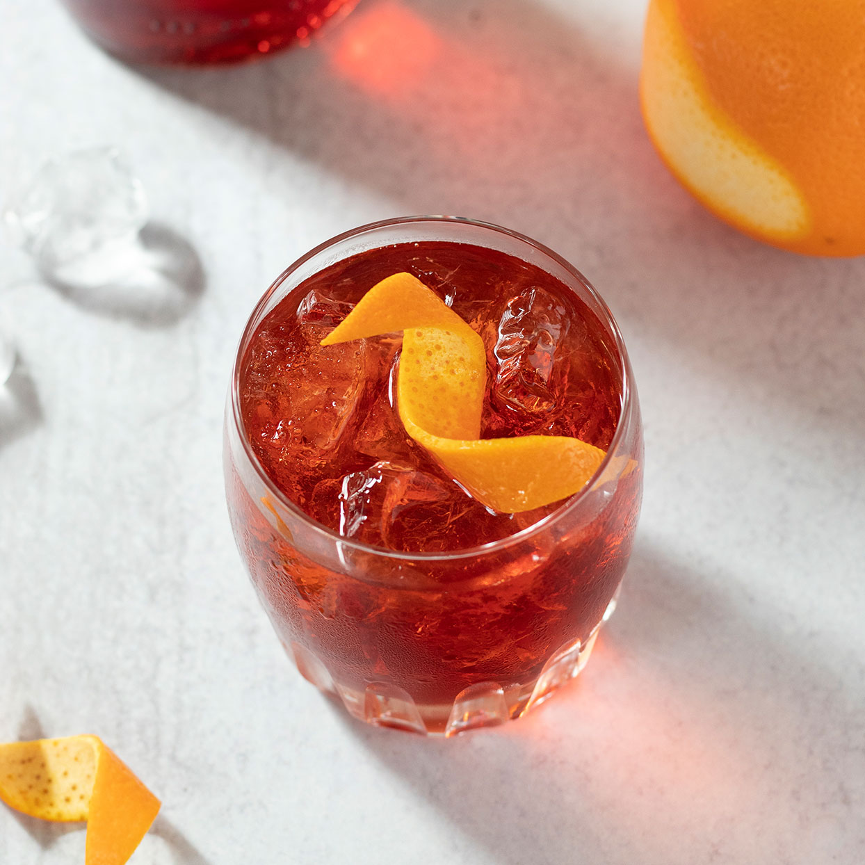 classic negroni shot in glass with orange peel twist on white background