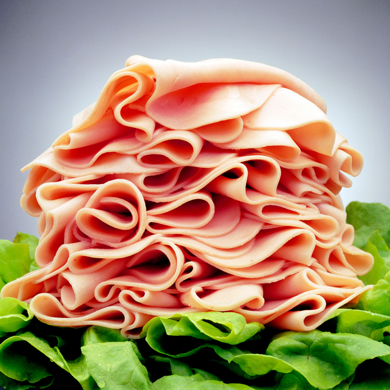 Closeup of a heap of ham on top of lettuce