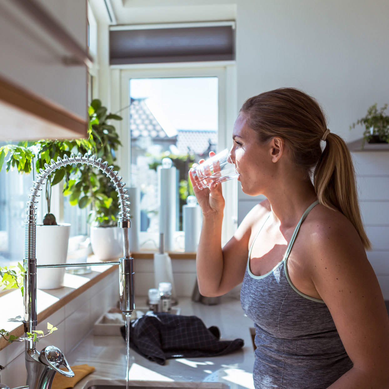 woman drinking a glass of water in a kitchen