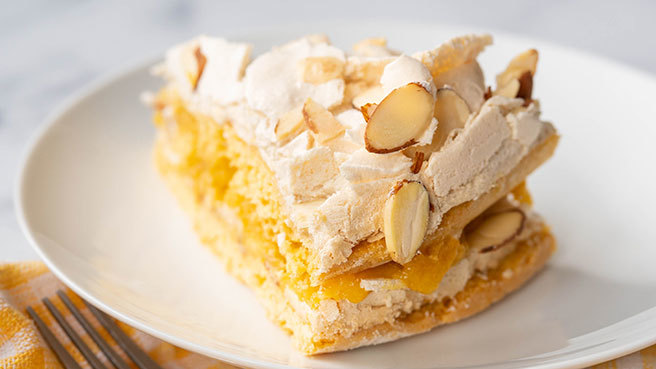 a slice of layer cake with orange filling and almonds