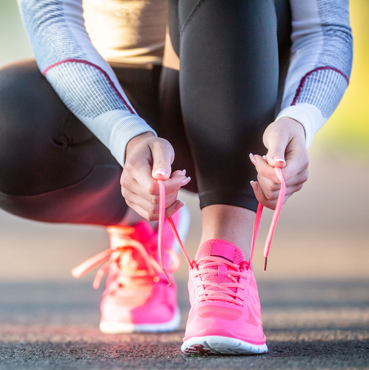 photo of woman lacing up pink running shoes outside