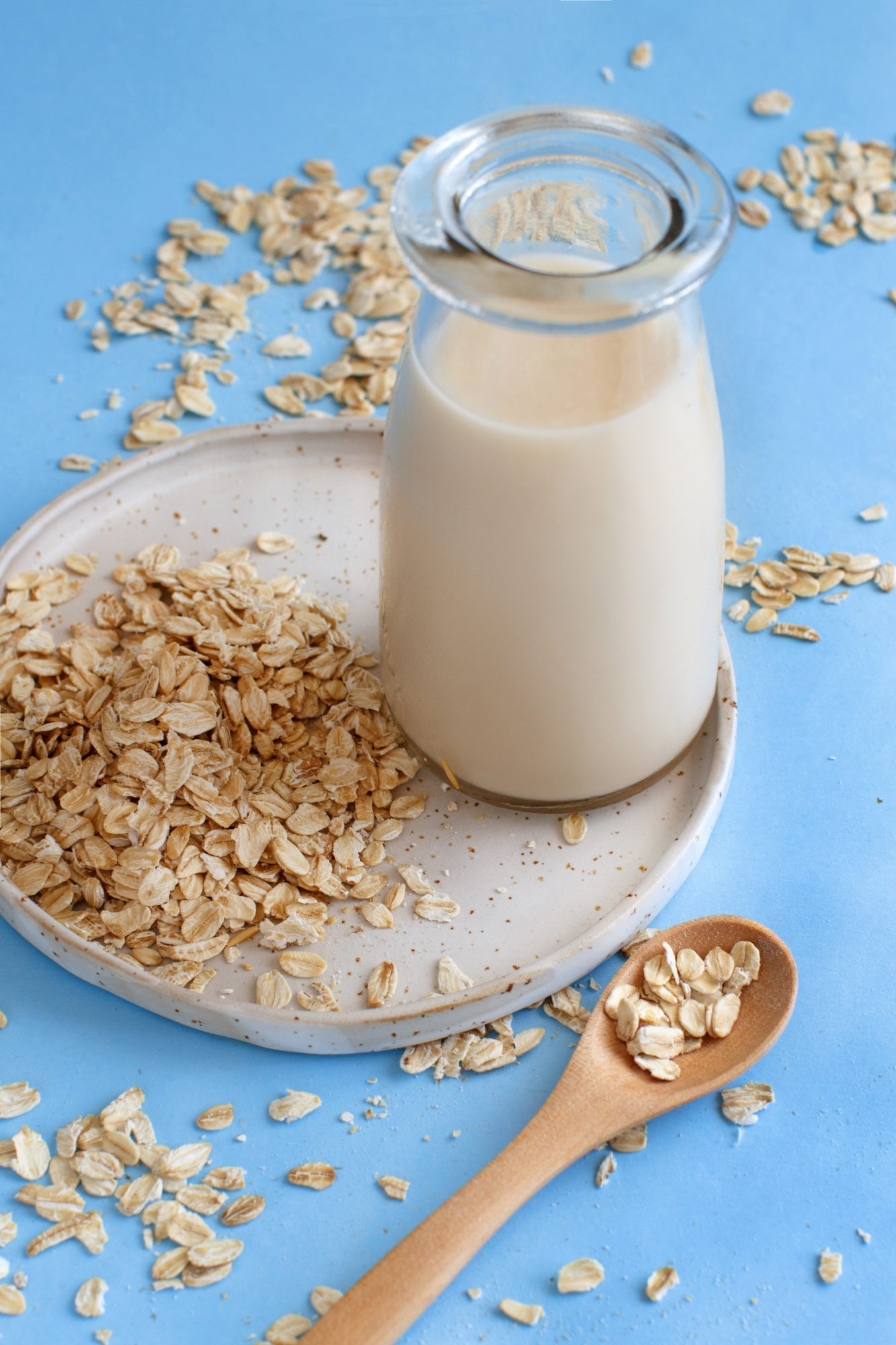 Bottle of oat milk and plate of oat flakes