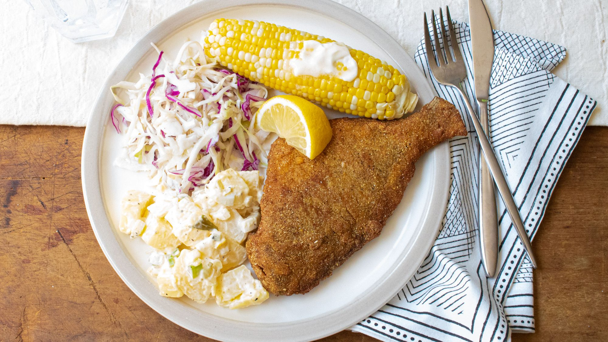 white plate with fried fish, coleslaw, potato salad and corn on the cob