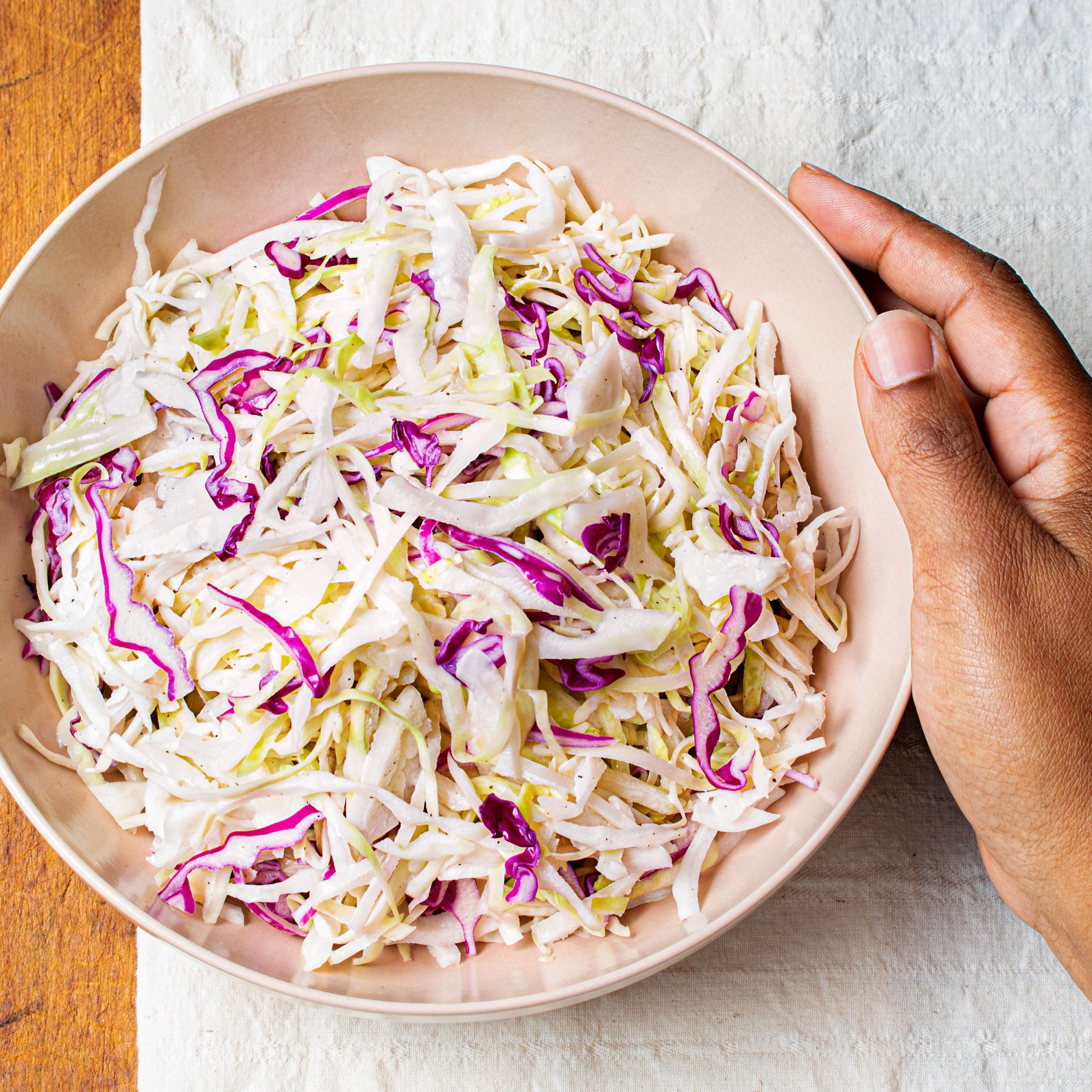 creamy coleslaw in a beige bowl with hand
