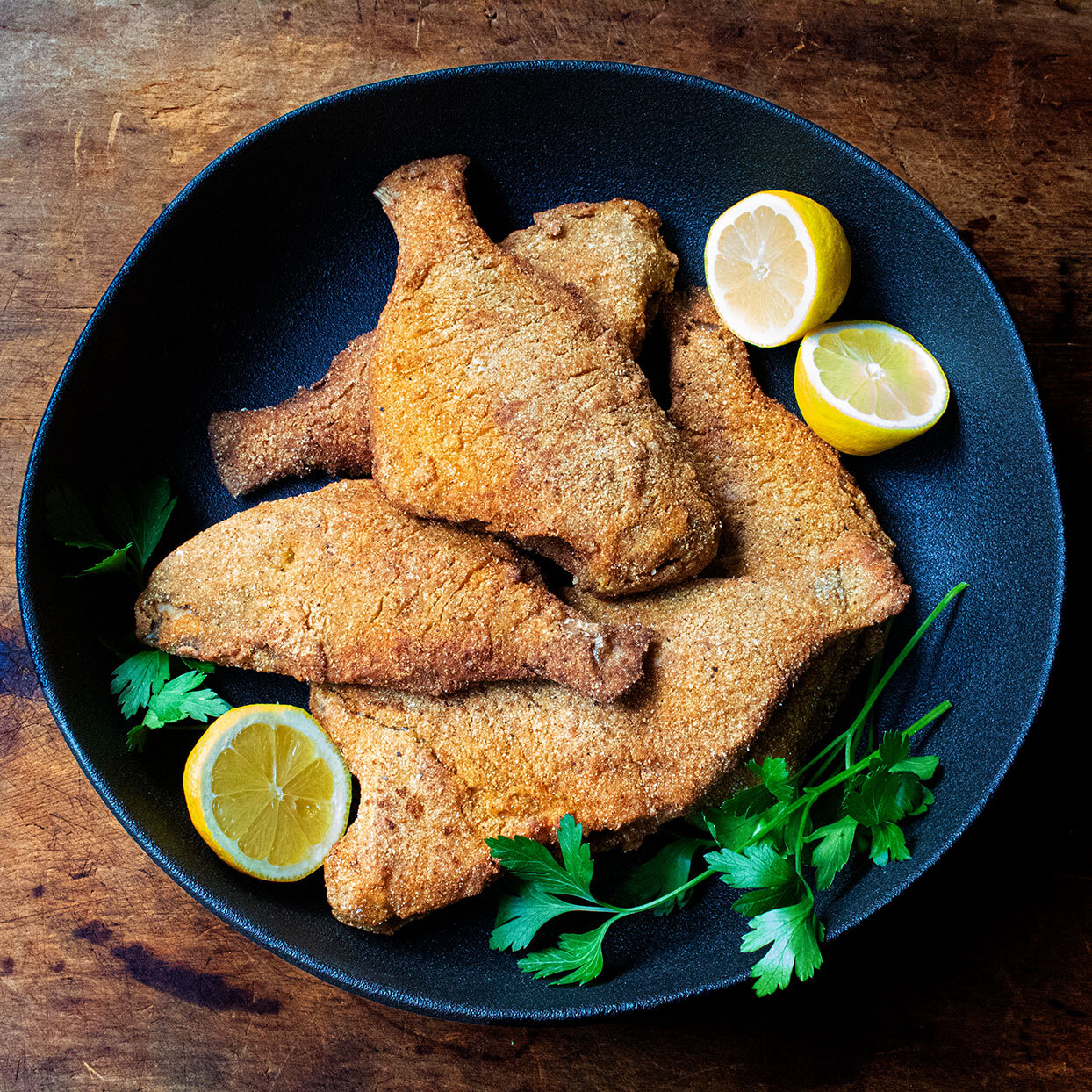 fried fish with lemon slices in a black bowl