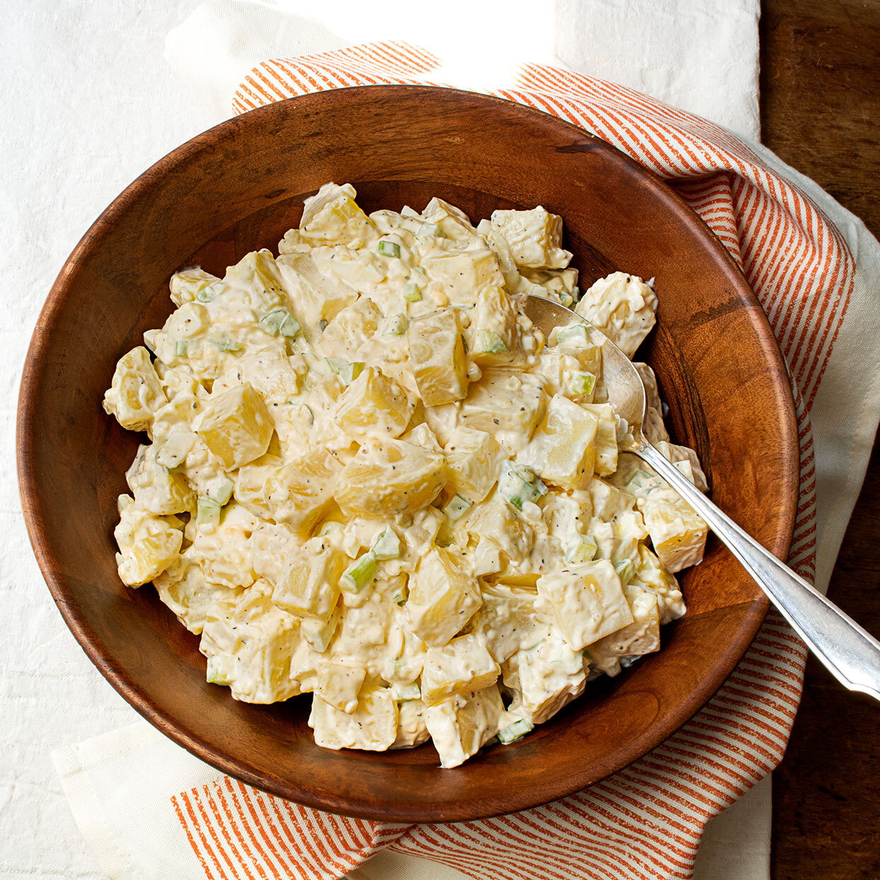 creamy potato salad with spoon in a wooden bowl