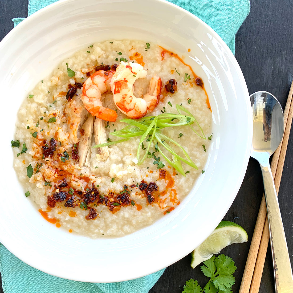 A bowl of congee with chicken, shrimp, lime and garnishes