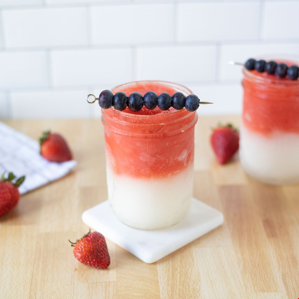 red and white layered frozen cocktail in a mason jar