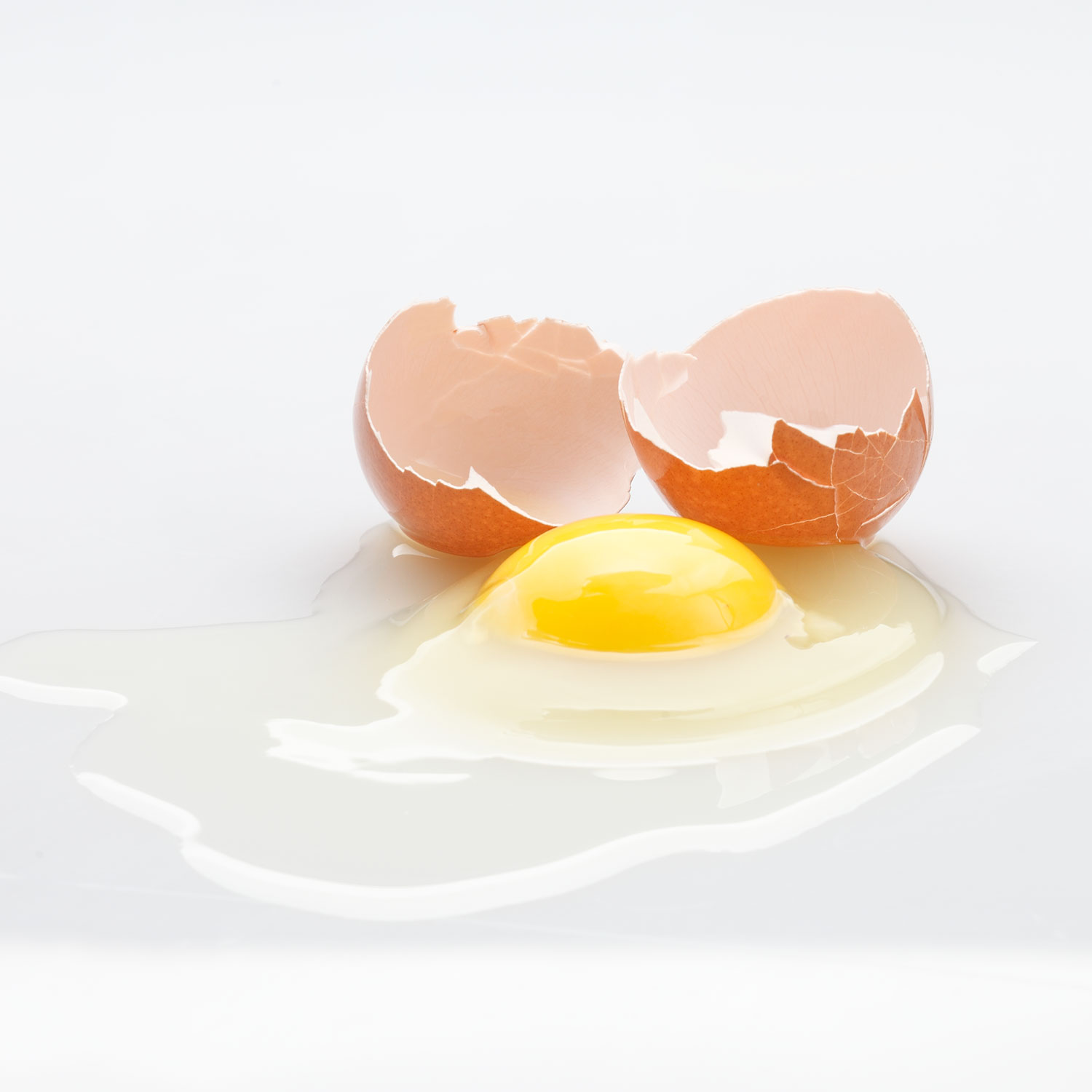 cracked raw egg on a white background