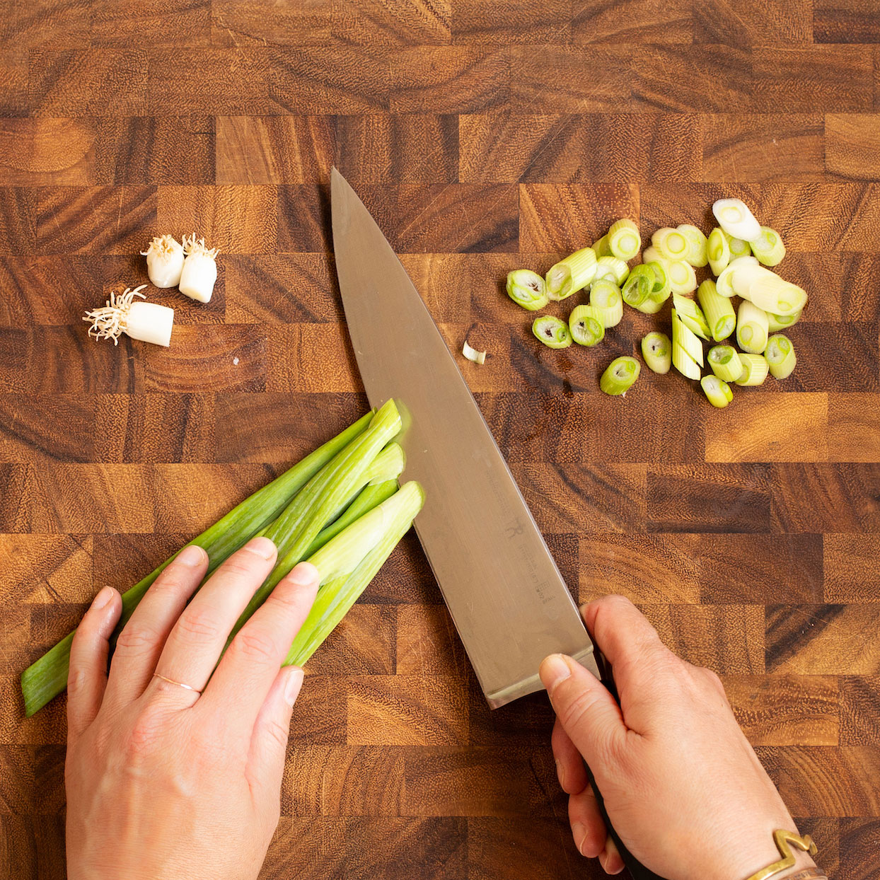 cutting green onions on the bias (diagonally) on a wooden cutting board