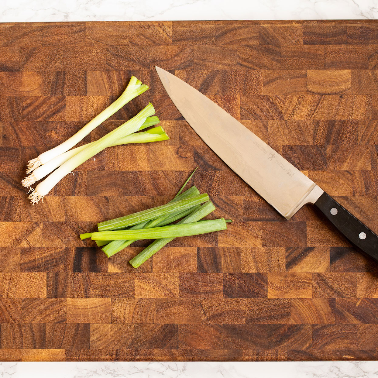 Sliced green onions on a wooden cutting board with knife