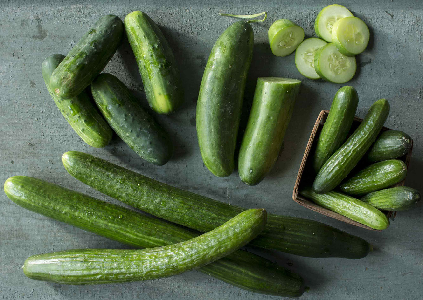 cut and whole raw cucumbers on a work surface