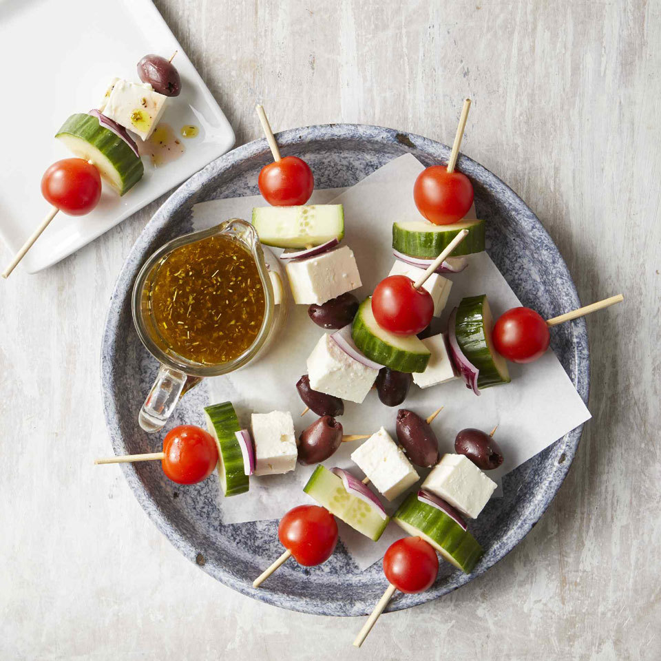 Greek Salad Skewers on blue plate on white background