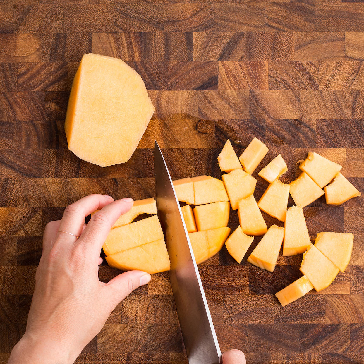 Cutting cantaloupe into cubes on a wooden cutting board