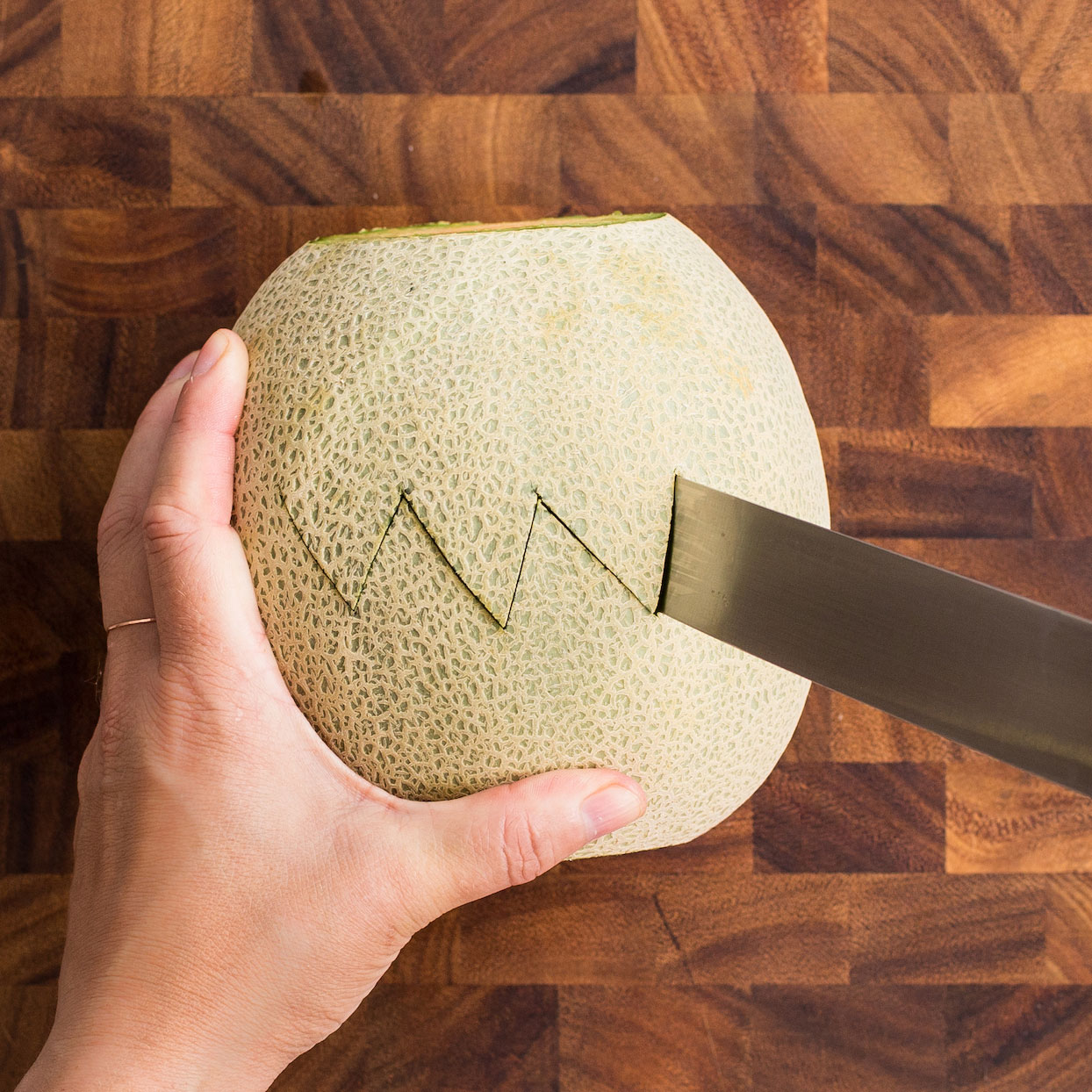 Cutting cantaloupe with a zigzag pattern on a wooden cutting board