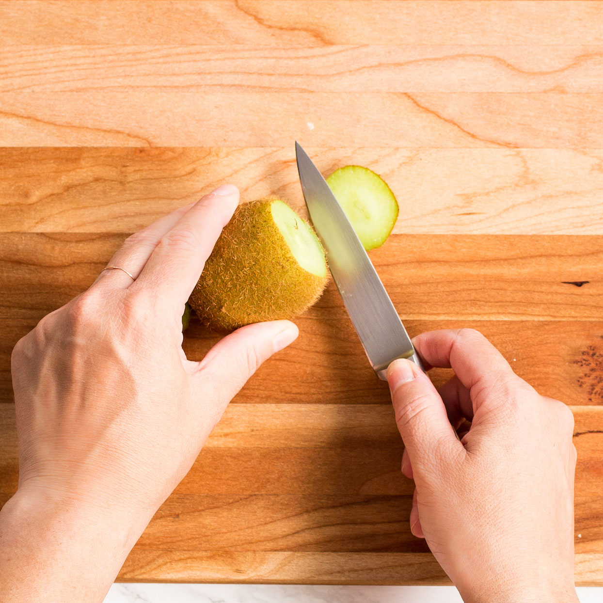 cutting the end off of a kiwi with a paring knife