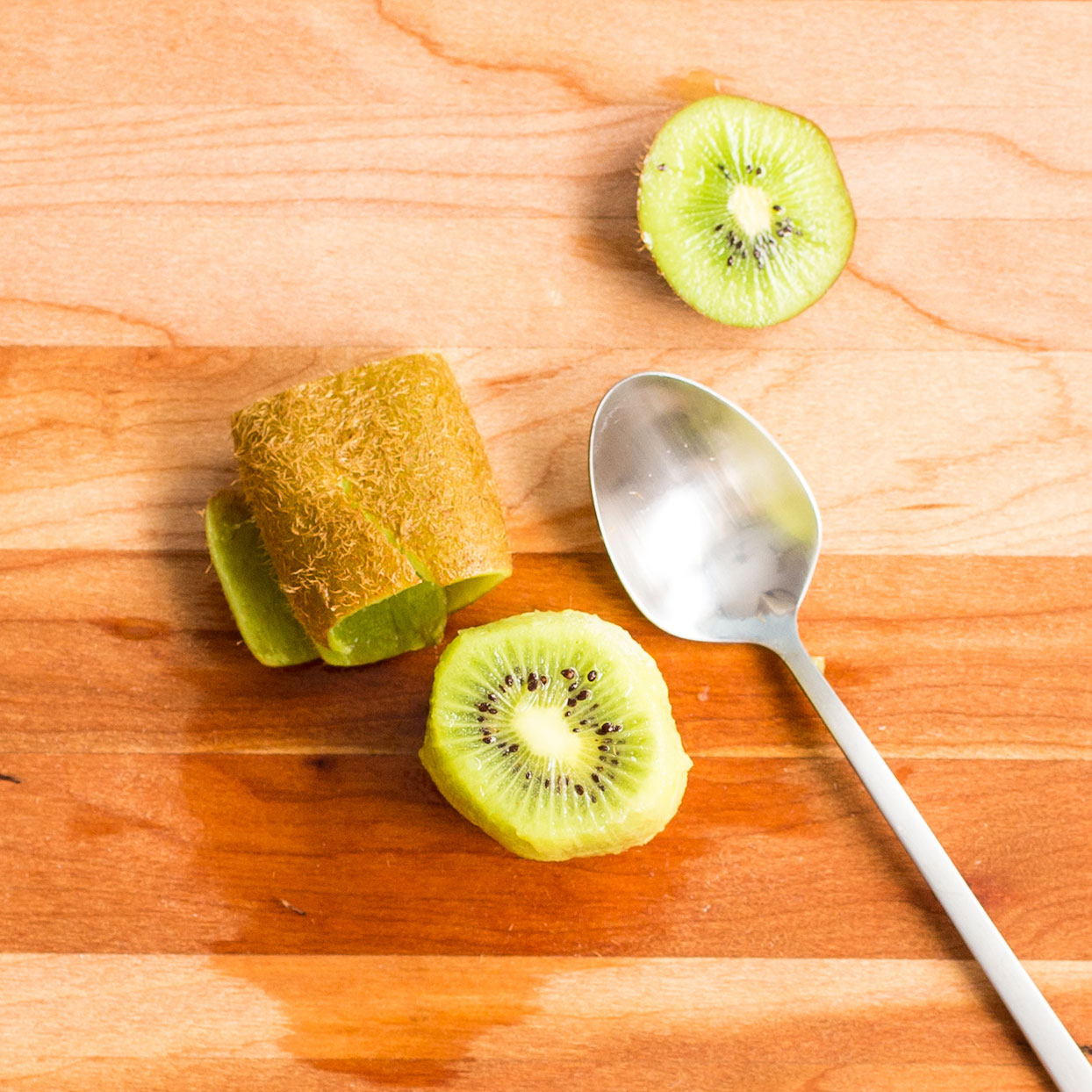 Peeled kiwi with a spoon