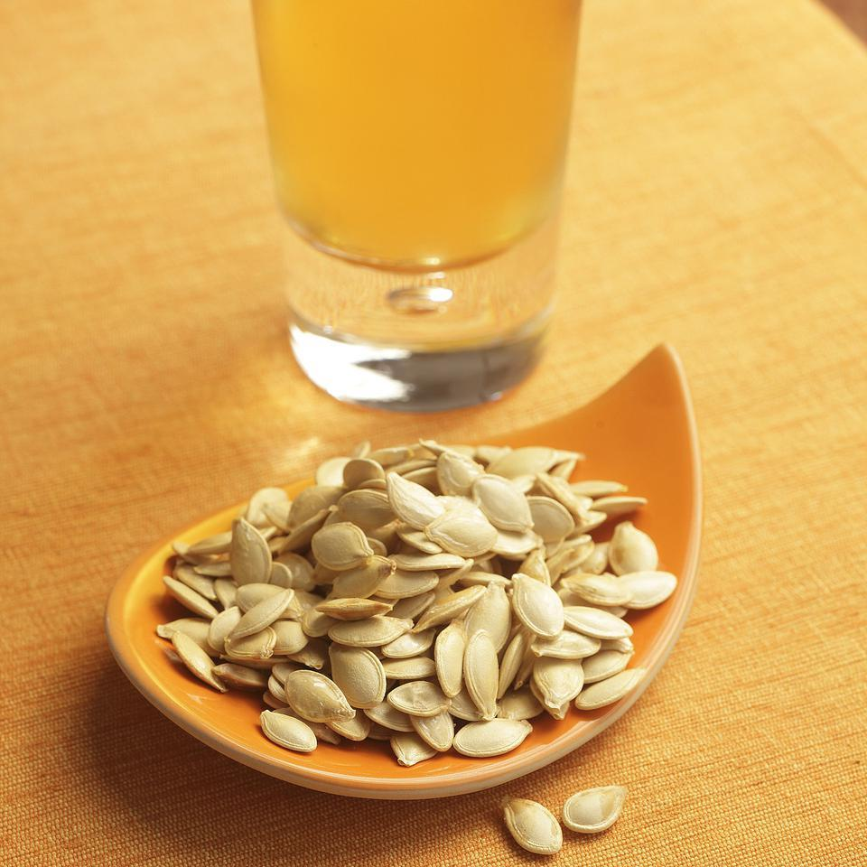 bowl of roasted pumpkin seeds in an orange bowl next to a pint of beer