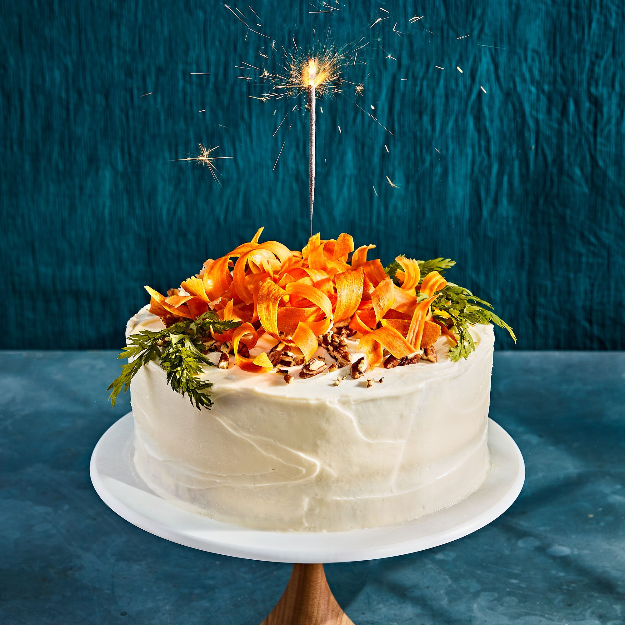 frosted cake topped with carrot peels with a sparkler on top on a deep blue background