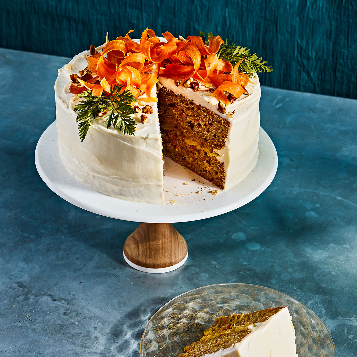 carrot cake on a white cake stand with a slice taken out against a blue background