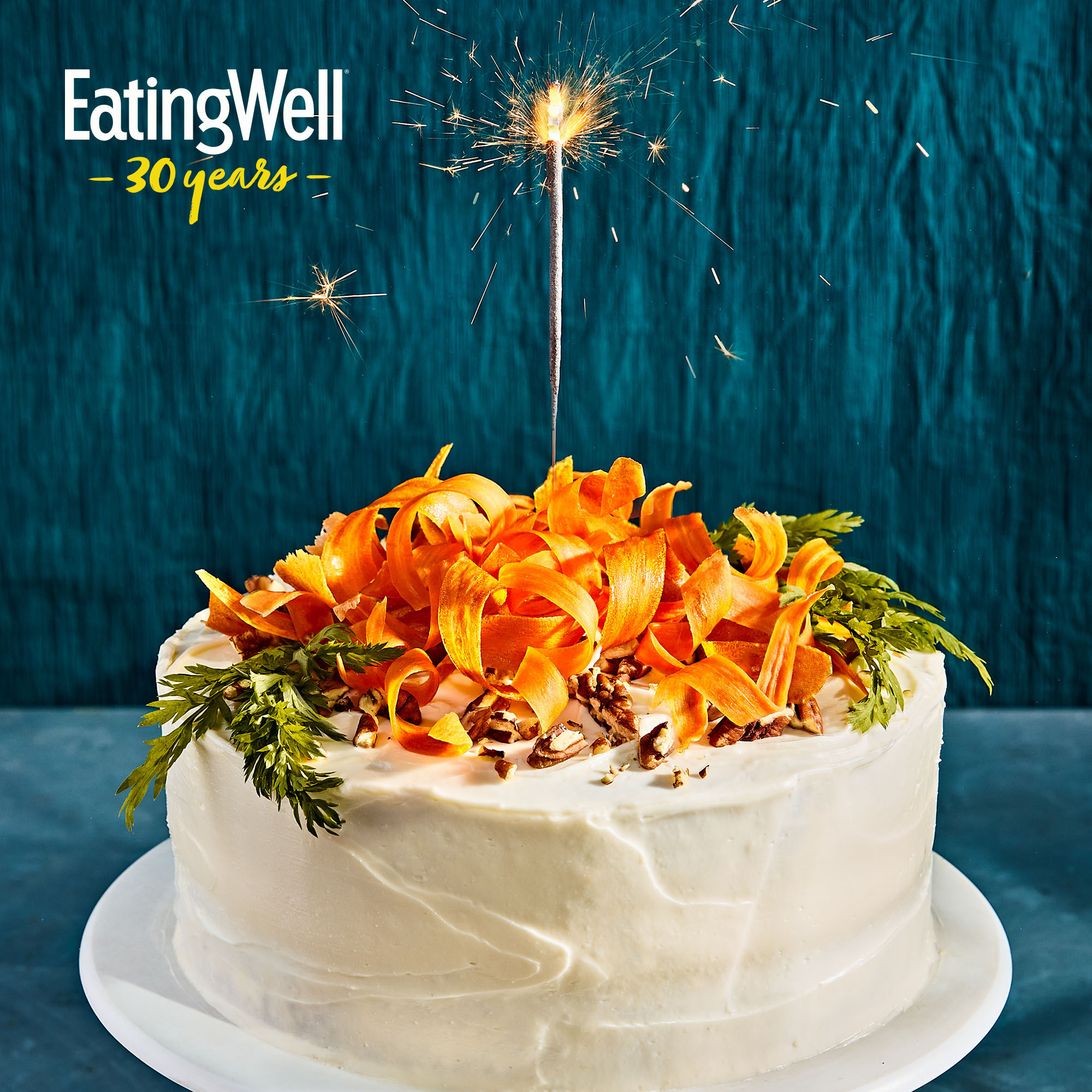 carrot cake with a sparkler on it against a blue background with EatingWell 30 years logo