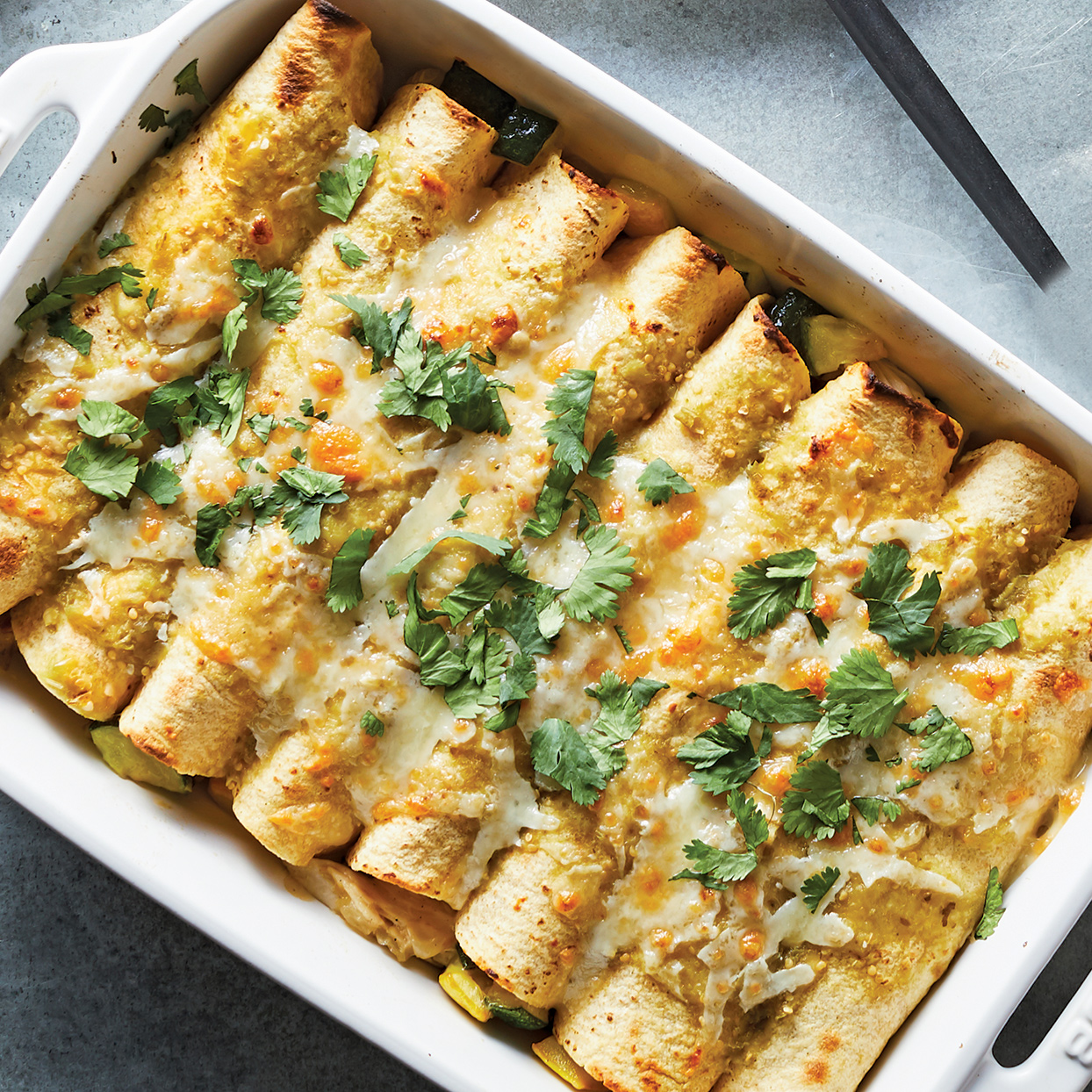 A dish of baked enchiladas with green herbs on top