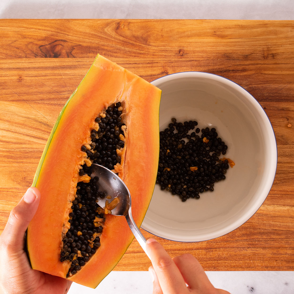 scooping seeds from a papaya with a spoon