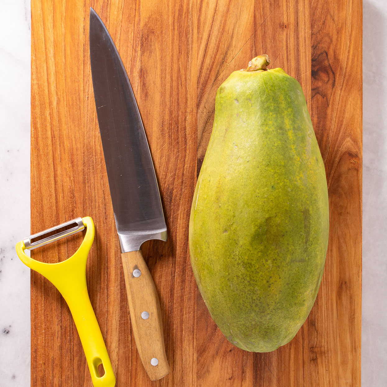 papaya, knife and peeler on cutting board