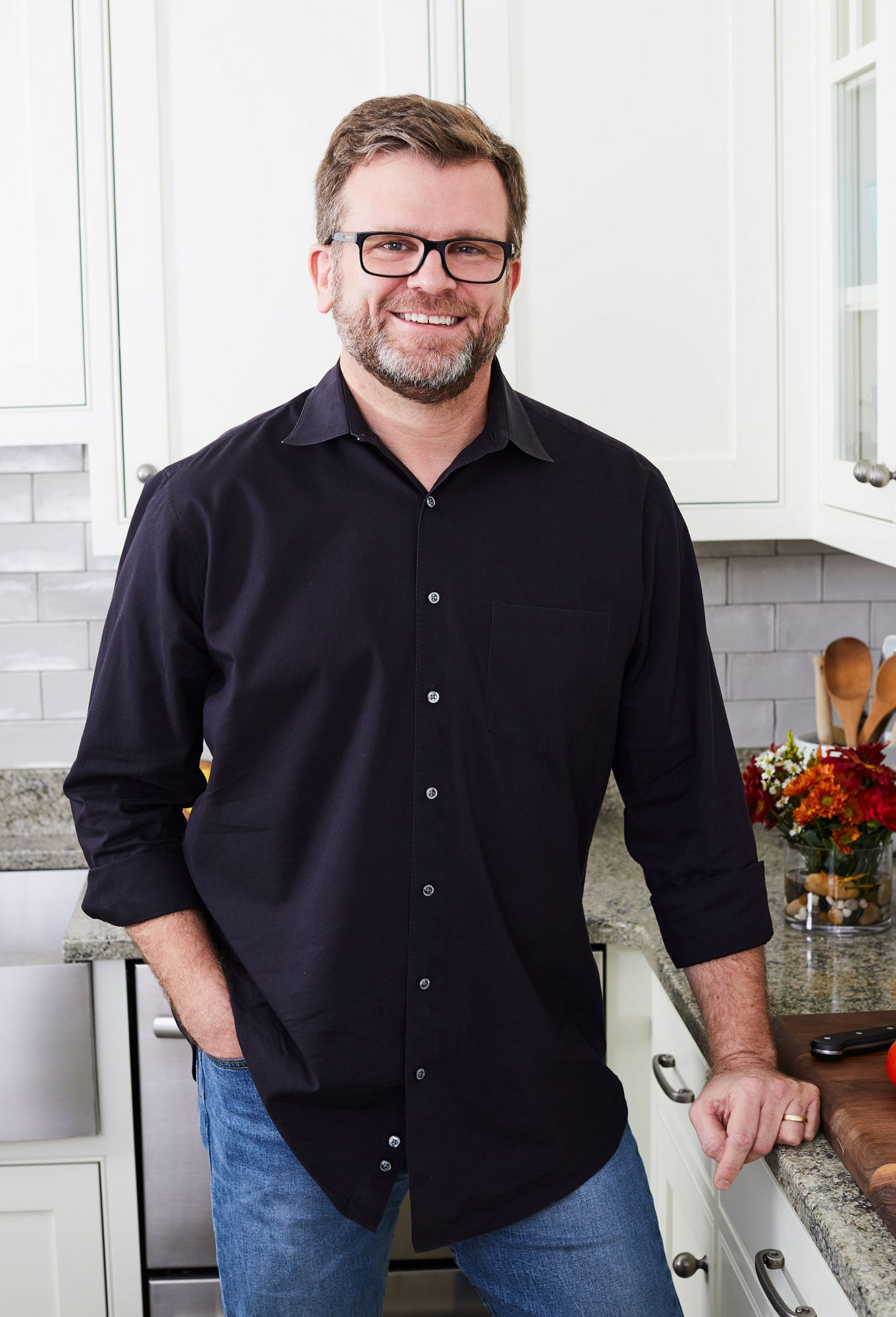 Profile photo of smiling man wearing a black button of shirt in a bright white kitchen