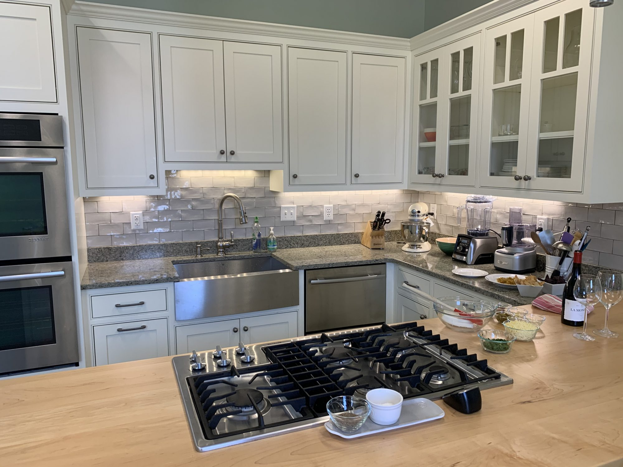 bright kitchen with cream colored cabinets and prepped food on a wooden counter