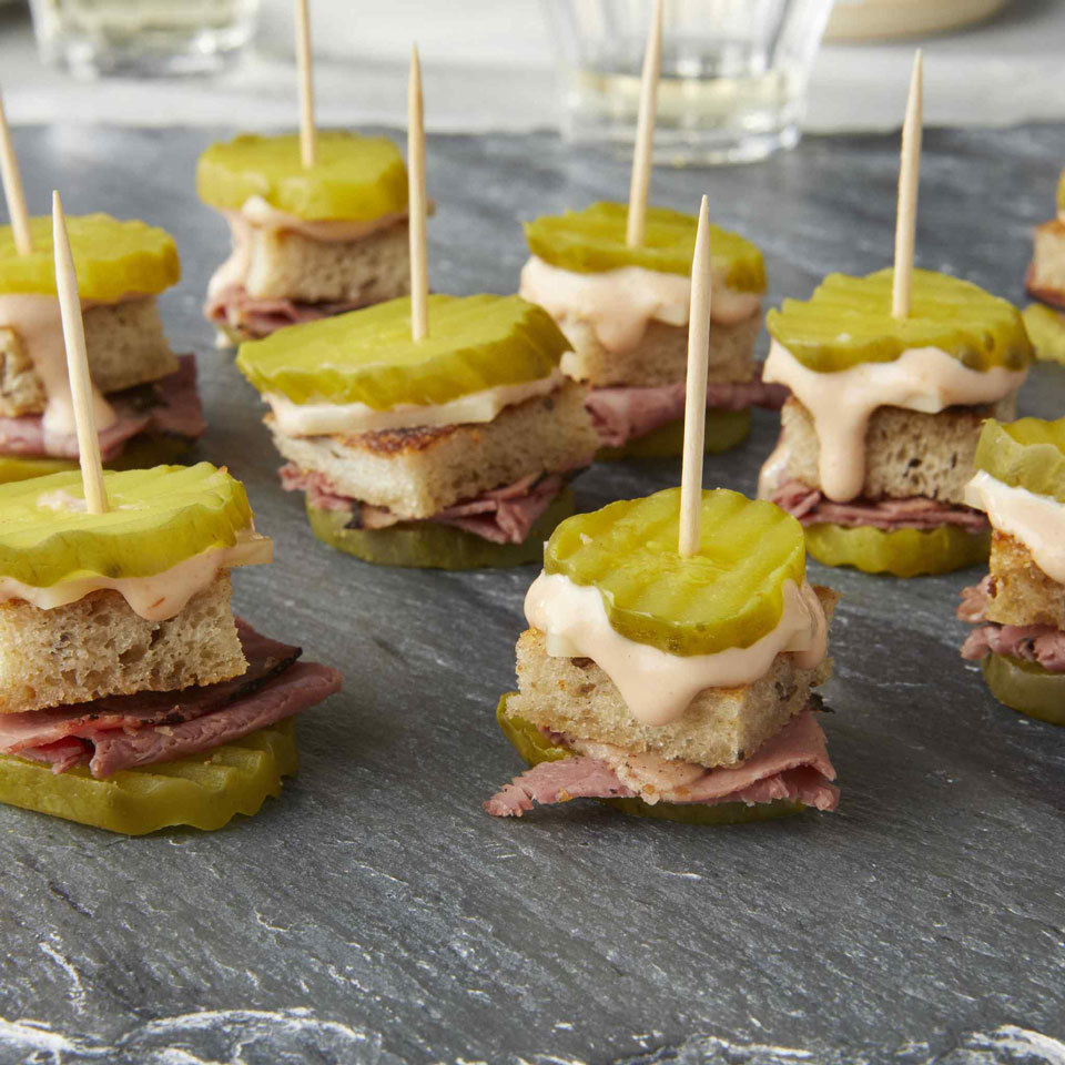stacks of pickles, bread, pastrami and cheese with a toothpick