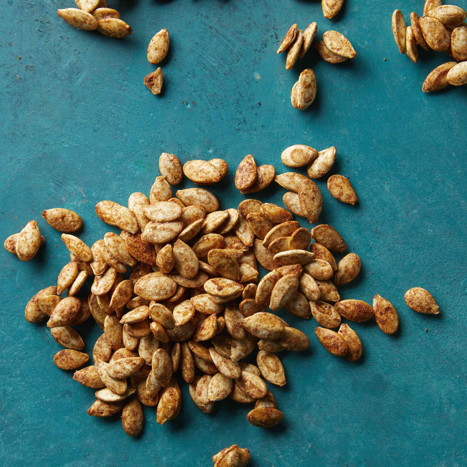 pile of roasted pumpkin seeds on a bright blue surface