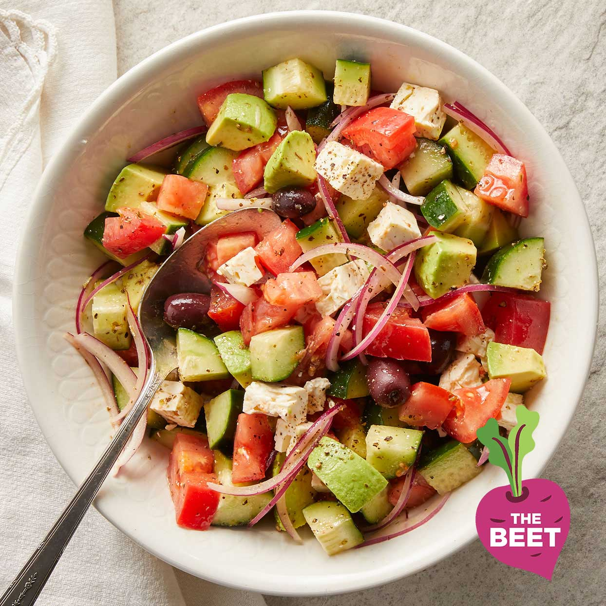 greek salad with chopped vegetables in white bowl with the beet logo overlaid in corner