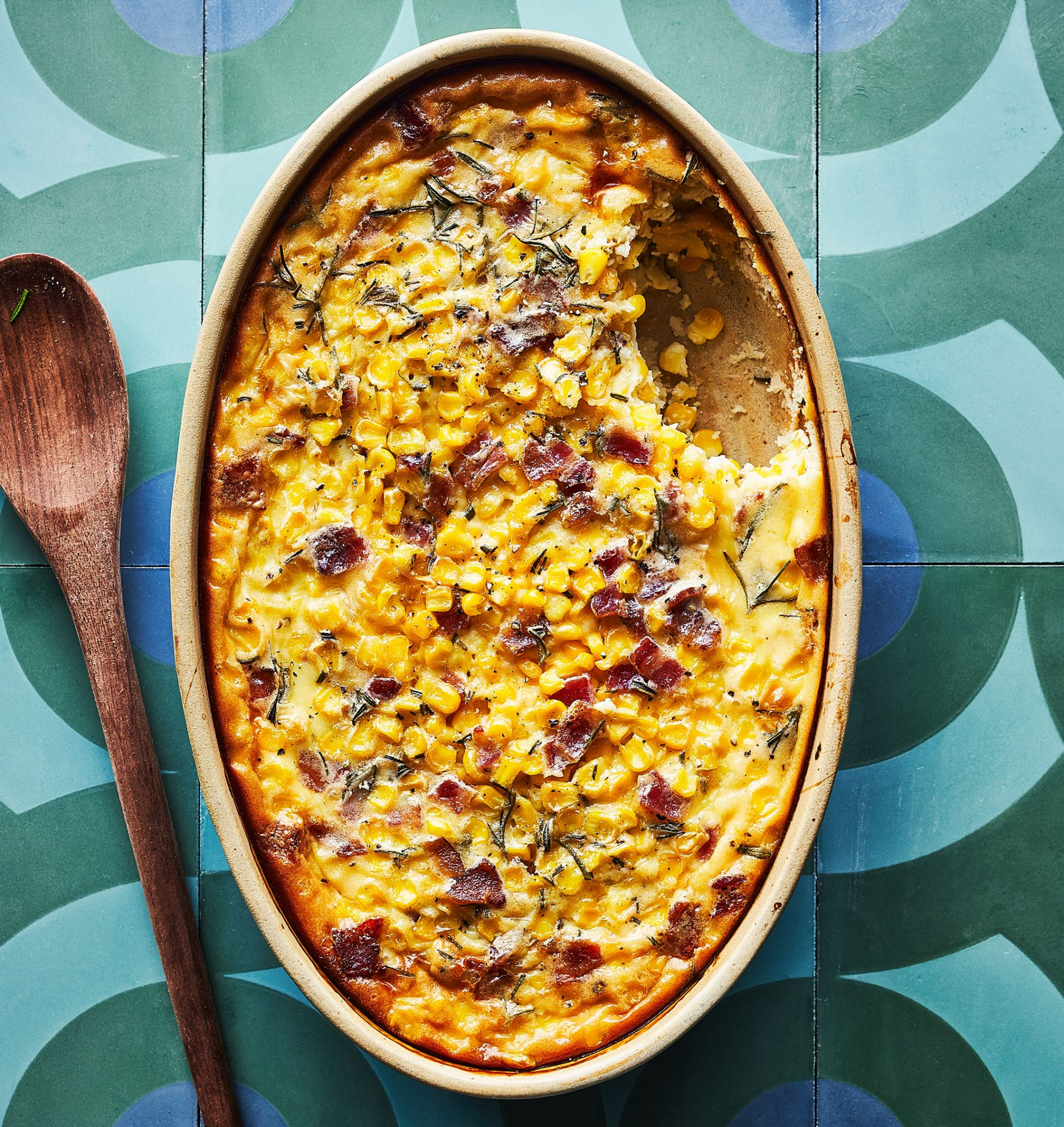 casserole dish with corn pudding on a green and blue tiled surface