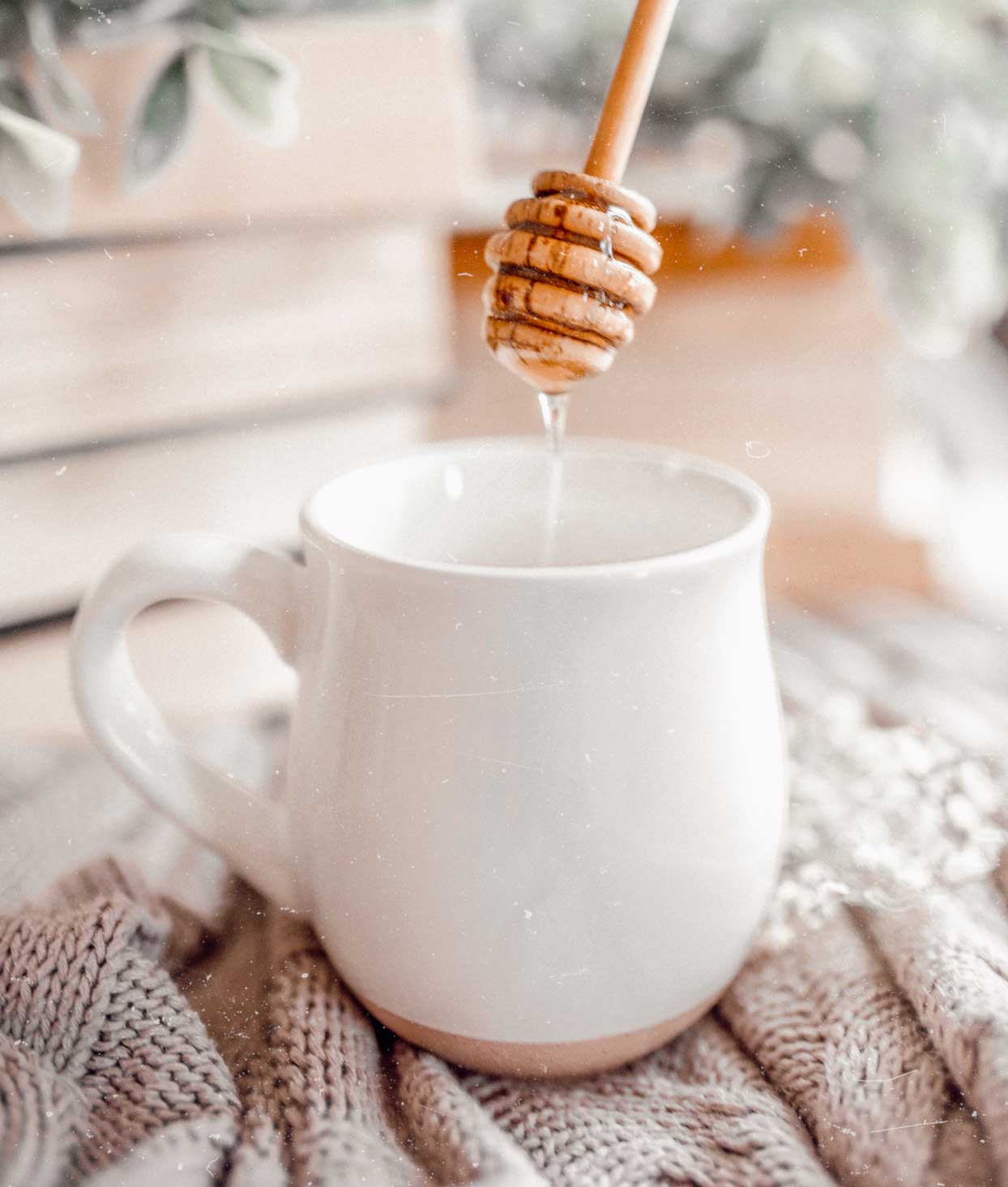 white mug of tea with honey dripping in