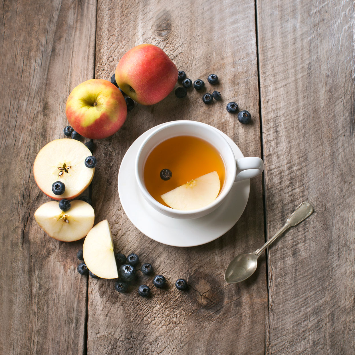 apples berries and tea on a wooden table