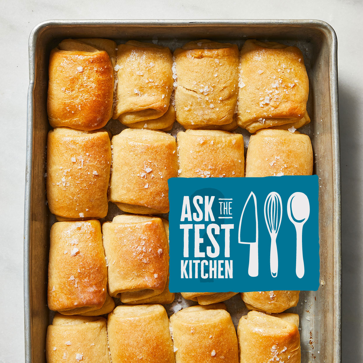 A pan of Parker House Rolls with an Ask the Test Kitchen Logo