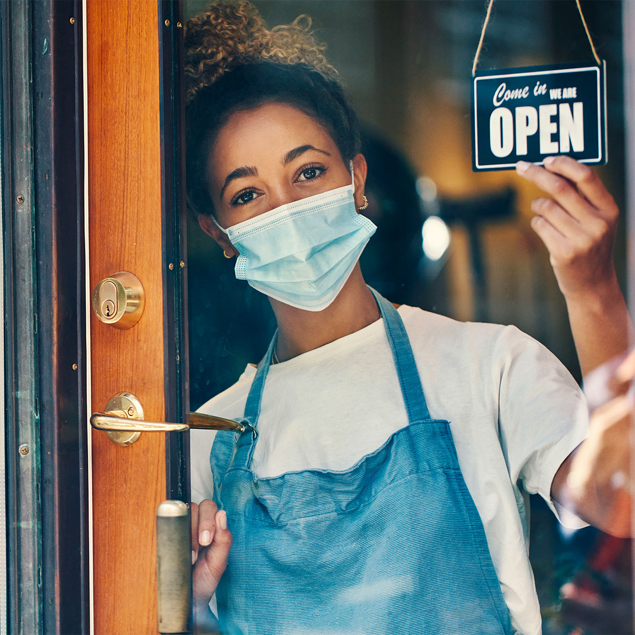 """woman with mask turning sign to say """"Open"""" through a glass door."""