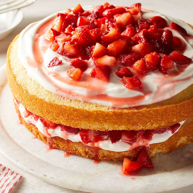 Sweet strawberries are nestled between layers of sponge cake and a cream filling in this easy cake. We add nonfat vanilla Greek yogurt to whipped cream to lighten up the filling and give it a little tang.