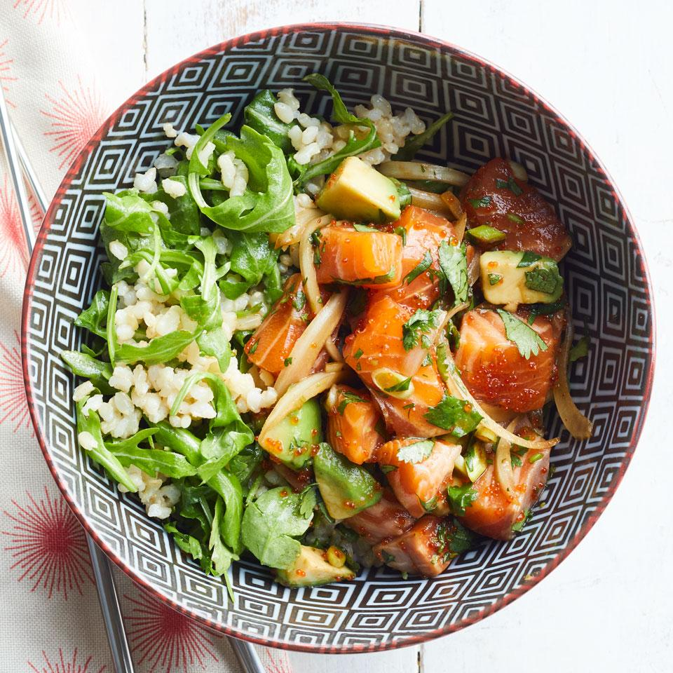 a bowl with salmon, avocado and greens